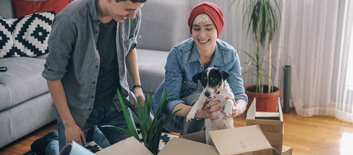 Happy young couple unpacking cardboard boxes at new home. They  enjoying their time while moving into new apartment with their dog.